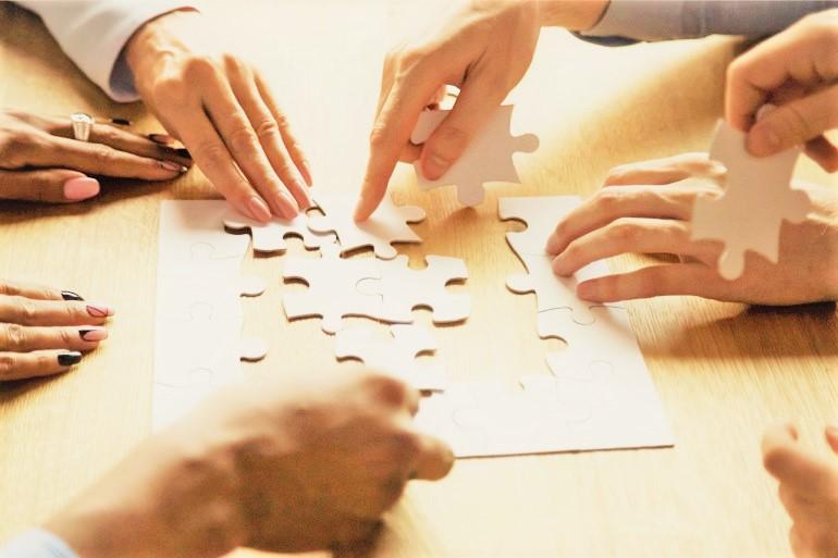 Team mit Puzzle beim Teambuilding
